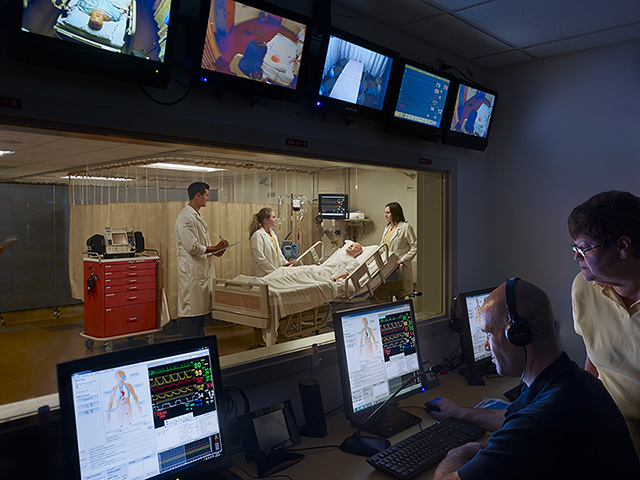 Three nursing students interact at the bedside of a simulated patient while two instructors observe remotely from a control room